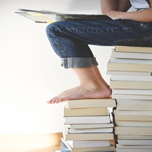 person sitting on top of stacks of books reading
