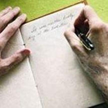 close up of hands writing in a notebook